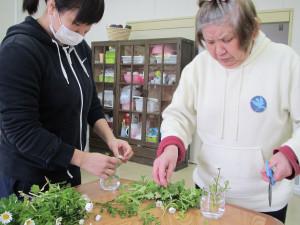 コーヒー喫茶に使うお花の準備をしている職員と利用者さん