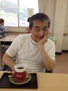 コーヒーを前にニヒルな笑みをしている利用者さん