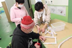 拭いたパッキンをはさみで切って、中の磁石を抜き取る作業をしている利用者